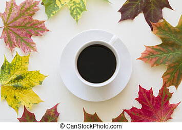 Cup of coffee, framed with autumn leaves on white background. Flat lay. Top view