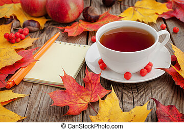 Cup of coffee, framed with autumn leaves on white background. Flat lay. Top view.