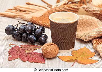 Grapes, cup of coffee, walnut, checkered plaid and dry leaves on wooden boards. An autumn still llife.