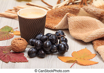 Cup of coffee, grapes, walnuts, checkered plaid and dry leaves on wooden boards. An autumn still llife.
