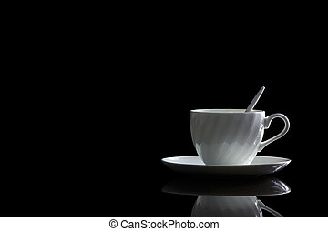 Cup of coffee in backlight on a black reflective background