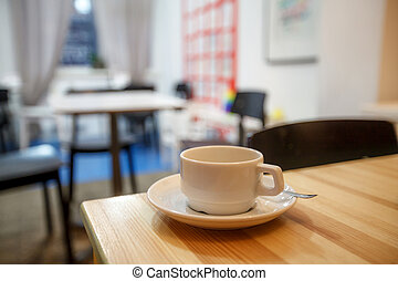 Cup of coffee in cafe on the table, blurred background