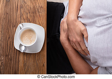 Cup Of Coffee In Front Of Man Having Stomach Pain