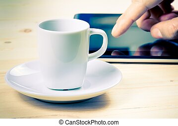 cup of coffee in front of the tablet on wood table, concept of new technology