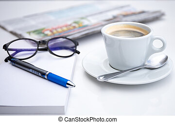 Cup of coffee in morning with notebook pen and glasses
