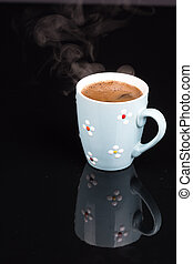 Cup of coffee isolated above black background with reflections