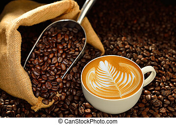 Cup of coffee latte and coffee beans on wooden table