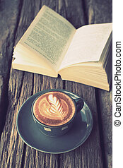 cup of coffee latte art on the wood desk and book in vintage...
