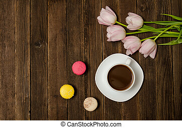 Cup of coffee, macarons and pink tulips on wooden background. Top view