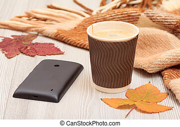 Cup of coffee, mobile phone, checkered plaid and dry leaves on wooden boards. An autumn still llife.