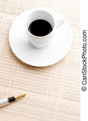cup of coffee near a golden pen
