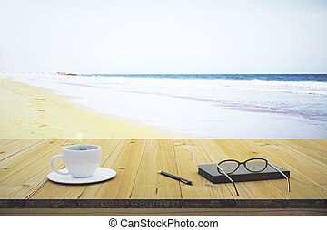 Cup of coffee notebook and glasses on a wooden table on the beach