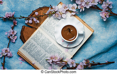 Cup of coffee on a book with cherry blossom branches