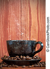 Cup of  coffee on a brown background with coffee beans