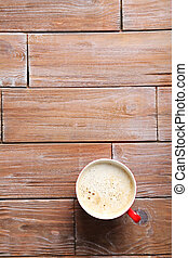 Cup of coffee on a brown wooden table