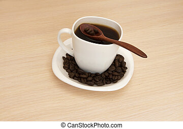 Cup of coffee on a table with a wooden spoon