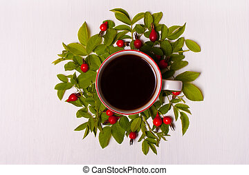Cup of coffee on a white background in leaves and red berries. Flat lay.