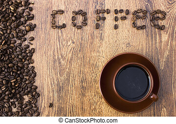Cup of coffee on a wooden background with coffee beans