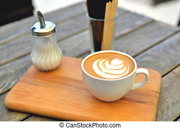 cup of coffee on a wooden stand is on the table in a cafe summer morning