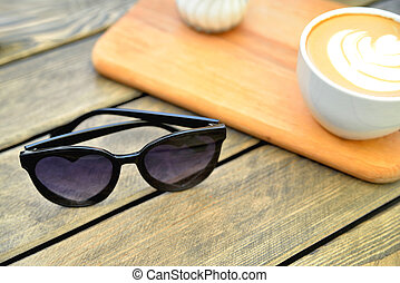 cup of coffee on a wooden stand is on the table in a cafe summer morning, sunglasses in the foreground