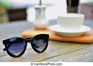 cup of coffee on a wooden stand is on the table in a cafe summer morning, sunglasses in the foreground,