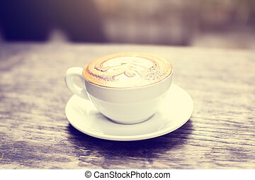 cup of coffee on a wooden table outdoors