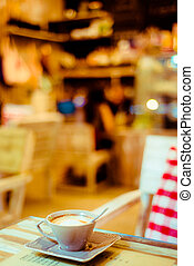 Cup of coffee on a wooden table with red pillow in cafe