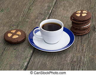 cup of coffee on an old table decorated with cookies