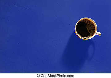 Cup of coffee on blue background, top view