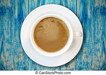 Cup of coffee on blue wooden surface