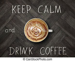 The cup of black coffee with cream is on the wooden floor with inscription keep calm and drink coffee.