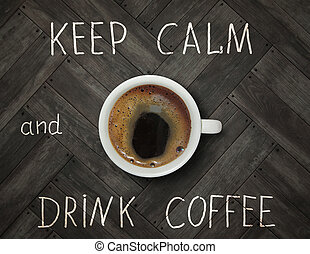 The cup of black coffee is on the wooden floor with inscription keep calm and drink coffee.
