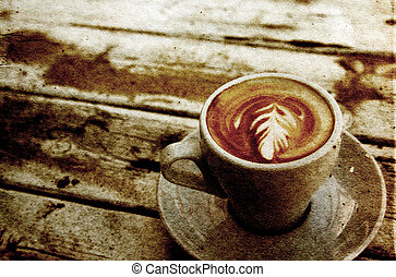 cup of coffee on old wooden table on the beach. Photo in old image style.