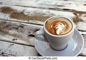 cup of coffee on old wooden table on the beach