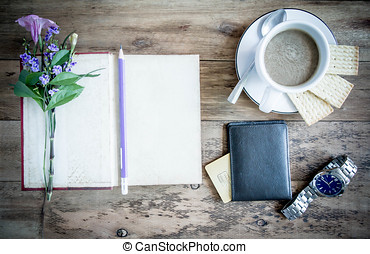 cup of coffee on rustic wooden table with open books