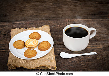 Cup of coffee on sackcloth napkin, on wooden table background