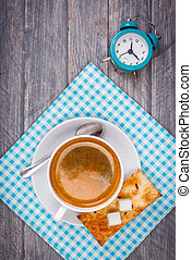 Cup of coffee on saucer with spoon. Blue napkin and alarm clock