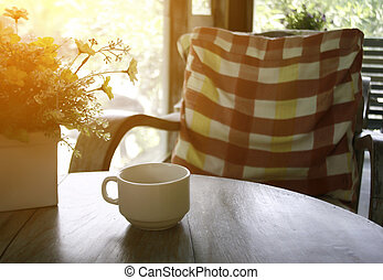 cup of coffee on table and chairs