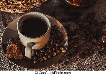 cup of coffee on textile with beans, dark candy sugar, pots, basket