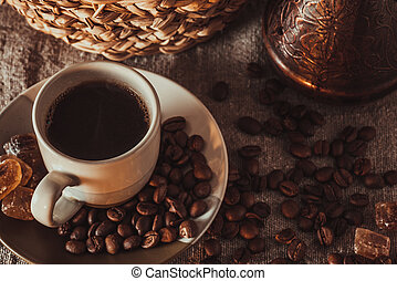 Cup of coffee on textile with beans, dark candy sugar, pots, basket and cake