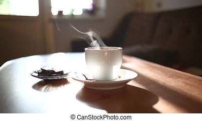 Cup Of Coffee On the table in living room. Hot Steam From The Cup Of Coffee On A light window