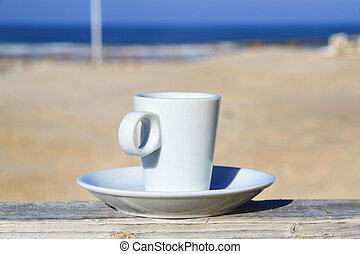 cup of coffee on the table with view on beach