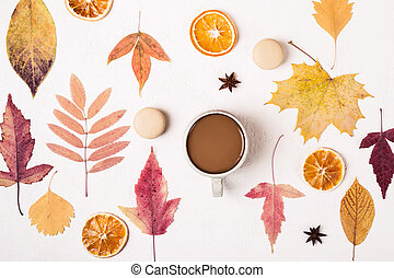 Cup of Coffee on white table with autumn leaves pattern