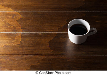 Cup of coffee on wooden background.