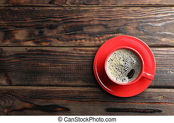 Cup of coffee on wooden background, top view
