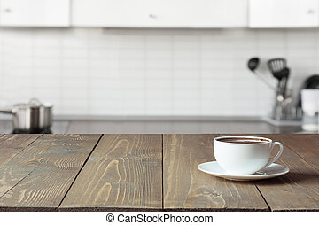 Cup of coffee on wooden board. Blurred kitchen as background.
