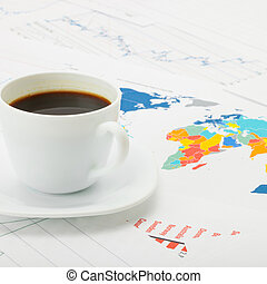 Cup of coffee over map and financial documents - studio sh