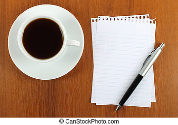 Cup of coffee, paper and pen on wooden background close-up