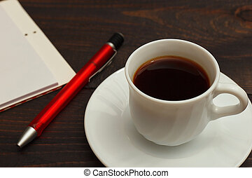 Cup of coffee, pen and notebook on wooden background