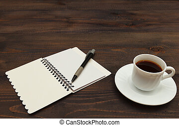 Cup of coffee, pen and open notebook on wooden desktop